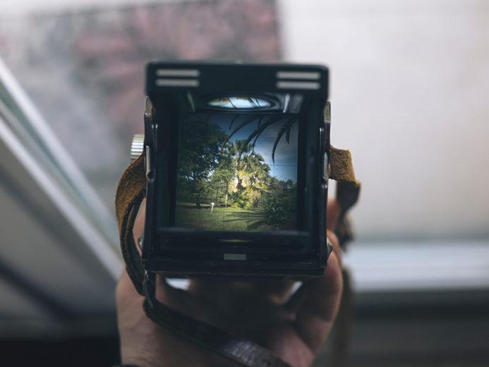 imagén cámara fotográfica en la mano de una persona que esta frente a una ventana imagen central de la pagina de Nuestro Festival